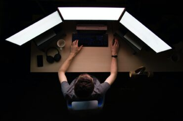 A man working with multiple monitors in a low light room