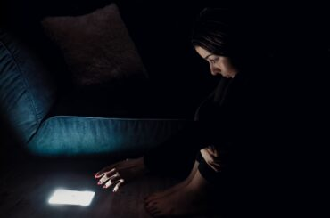 Young woman in black dress trying to stay away with shiny smartphone in the dark
